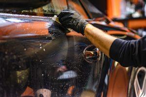Homme ganté en train de nettoyer sa voiture à l'eau