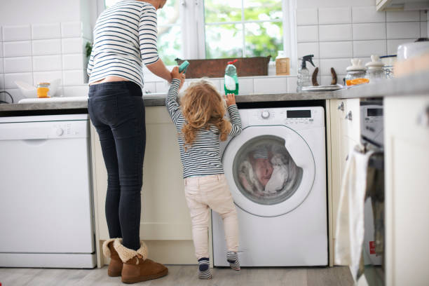 Jeune maman qui fait la vaisselle avec sa petite fille