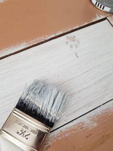 un pinceau qui peint une planche de bois en blanc