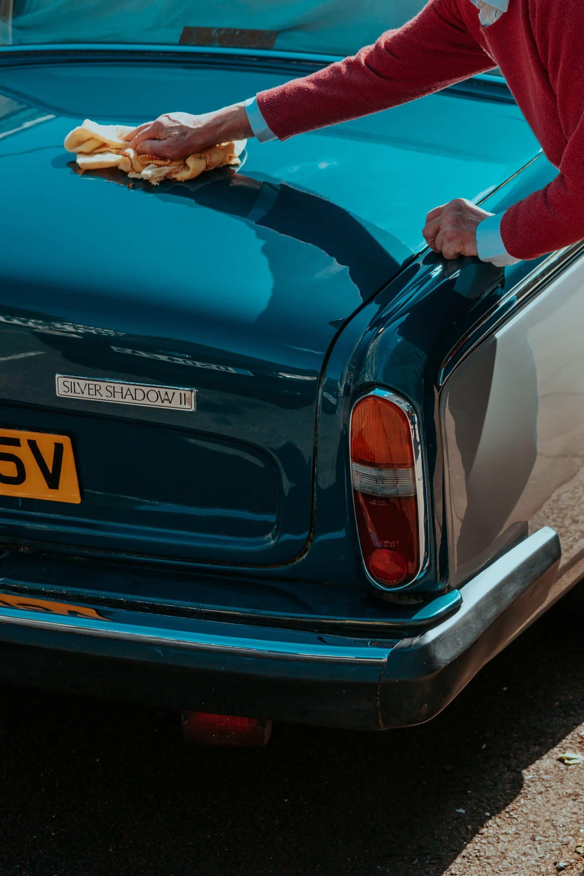 Homme en train de nettoyer sa voiture de luxe avec un chiffon