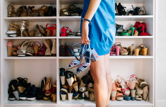femme tenant des chaussures devant un placard rempli de chaussures