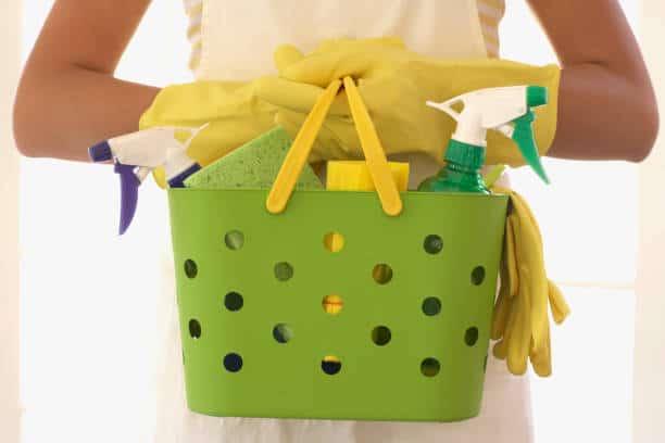 Gros plan sur un panier vert avec produits ménagers que tient une femme aux mains gantées