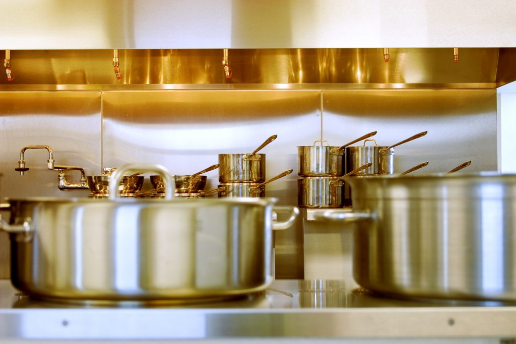 La cuisine d'un réstaurant avec une batterie de casserolles en inox