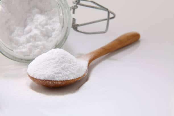 Pot et cuillière de bicarbonate de soude pour enlever tache de gras