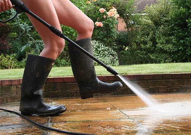 Jeune femme en bottes en caoutchouc en train de nettoyer sa terrasse en carrelage avec un jet d'eau