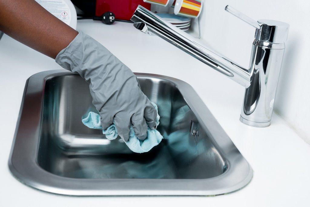 main gantée qui nettoie un évier